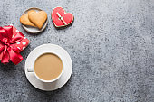 Valentines day card with heart cookies, love letter, coffee cup on grey table.