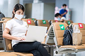 Young female wearing face mask and using computer laptop in airport, protection Coronavirus disease infection, Asian woman traveler sitting on chair. New Normal, social distancing and digital nomad