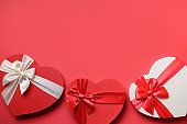Valentine's Day frame of red hearts gifts on red. Flat lay. Romantic greeting card.