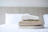 Stack of beige wool Sweaters on bed in luxury hotel or resort or home. Relax, autumn or winter clothes, laundry and vacation concepts