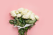 Bouquet of white roses on pink. Top view, copy space.