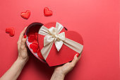 Valentine's Day heart box in woman hands on red. Romantic greeting card with copy space.