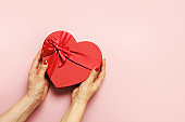 Valentine's Day romantic heart box in woman hands on pink. View from above. Flat lay. Greeting card.