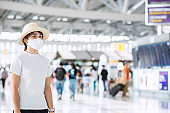Young adult female wearing face mask in airport terminal, protection Coronavirus disease infection, Asian woman traveler ready to travel. New Normal and travel under COVID-19 concept