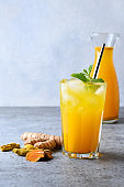 Golden milk turmeric iced freshness latte garnish mint. Ayurvedic drink on light background. Vertical format.