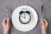Hands holding knife and fork above alarm clock on white plate on tablecloth background. Intermittent fasting, Ketogenic dieting, weight loss, meal plan and healthy food concept