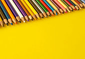 Set of colored pencils next to each other on the yellow background, top view.