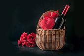 Valentines day gift hamper, bouquet of red roses, bottle of sparkling wine on black.