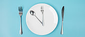 Top view white ceramic plate with knife, spoon and fork on blue background. Intermittent fasting, Ketogenic dieting, weight loss, meal plan and healthy food concept