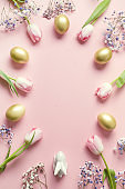 Easter frame of pink tulips, golden eggs and bunny on pastel pink. Top view with copy space.