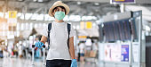 Young woman traveler wearing face mask and nitrile glove holding handle luggage in airport terminal, protection Coronavirus disease (Covid-19) infection. New Normal and travel bubble concept