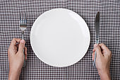 Hands holding knife and fork above white plate on table background., dieting, weight loss, dining and kitchenware concept