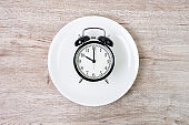 Top view alarm clock on white plate on wooden table background. Intermittent fasting, Ketogenic dieting, weight loss, meal plan and healthy food concept