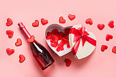 Valentine's Day box in shape of heart and sparkling wine on pink. View from above. Flat lay.