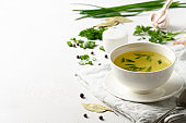 Chicken broth with green onion in white bowl on white table. Copy space.