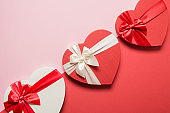 Valentine's Day romantic hearts gifts on red background. Flat lay. Greeting card with copy space.
