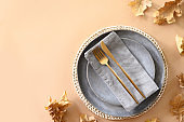 Fall table setting with autumn oak leaves and golden cutlery on grey background. View from above, space for design.