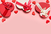 Valentine's Day concept with red boxes and hearts on pink.