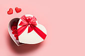 Valentine's Day romantic box in shape of heart with red bow on pink.