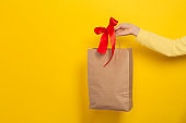 Female hand hold large gift bag made of brown craft paper with a red bow on yellow background.