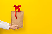Female hands hold large gift pocket made of brown craft paper with a red bow
