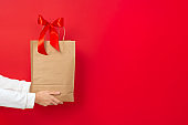 Female hand hold large gift bag made of brown craft paper with a red bow isolated on red background