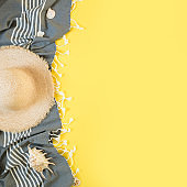 Beach straw sun hat, seashells on yellow background. Square Summer holiday background. Top view.