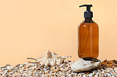 Brown glass bottle for soap or shampoo on stone and shell sand. Monochrome creative composition on beige.