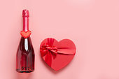 Valentines day greeting card. Bottle of sparkling wine with gift box shaped heart with red bow on pink. Top view. Space for text.