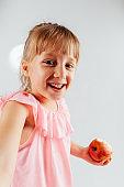 Portrait of playful little girl holding apple