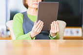 Japanese senior woman looking at tablet device