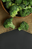 Fresh Broccoli in wooden bowl and seed oil in rustic style. Close up on a black background. copy space for text. Top view, flat lay