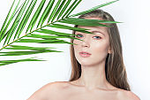 Natural organic skin care, the concept of harmony with nature, green long fern leaves grass near the face. portrait of beauty ladies. Young beautiful woman with clean sparkling skin of face and body