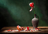 Classic still life with beautiful red tulip flower in old vintage jug and with pomegranate fruit on old wooden table in ray of light on green background. Art photography.