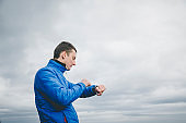 Man using a smart watch while hiking in the mountain