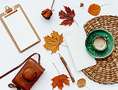 Trendy flat lay composition with coffee cup, old retro camera and autumn leaf, Office table with clip board, blogger concept