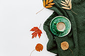 Flat lay with Coffee cup and autumn fall leaves on white background