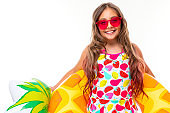 bright portrait of a girl in a swimsuit in sunglasses with a swimming circle in the form of pineapple