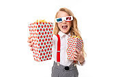 A little girl with makeup and long blonde hair, 3d glasses looks film or cartoon with popcorn isolated on white background
