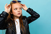Pretty caucasian teenager girl with long brown hair in black jacket and denim jeans holds black sunglasses isolated on blue background