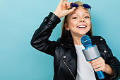 Caucasian teenager girl with brown hair in black jacket, blue sunglasses with blue microphone isolated on blue background