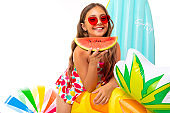 girl with a piece of watermelon on the background of air mattresses, balls and circles