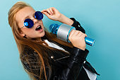 Nice girl in black jacket, blue sunglasses sings songs with blue microphone isolated on blue background