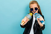 Caucasian teenager girl with brown hair in black jacket, blue sunglasses sings songs with blue and yellow microphones isolated on blue background
