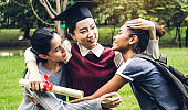Successful of student young woman and bachelor gowns with diplomas graduate hugging her friend at university.Celebrating graduation and education concept