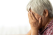Senior adult elderly asia women serious depressed and feeling headache, thinking of problems on white background