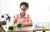 Teenage girl students learning and doing a chemical experiment and holding test tube in hands in science class on the table.Education concept