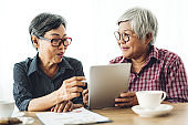 Portrait of two friend happy senior adult elderly asia women smiling and working with digital tablet computer at home.Retirement concept
