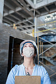 Portrait of an architect wearing a facemask while working at a construction site