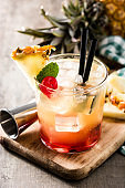 Cold mai tai cocktail with pineapple and cherry